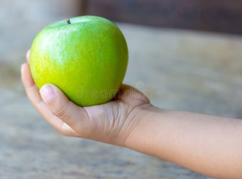 De baby houdt een groene appel op een houten achtergrond, Close-up stock foto
