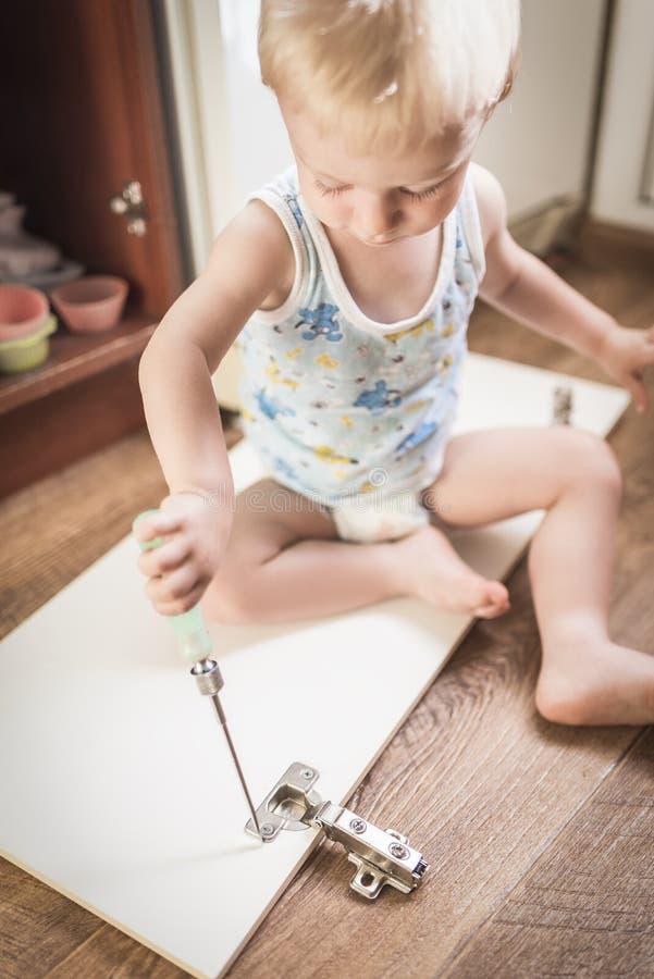 De baby houdt een schroevedraaier en herstelt meubilair royalty-vrije stock afbeelding