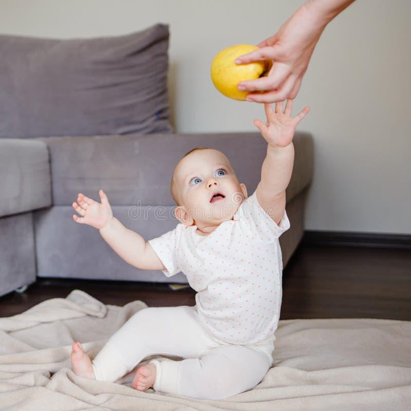 De baby krijgt een appel van moeder De moeder geeft aan dochter haar eerste voedsel royalty-vrije stock afbeeldingen