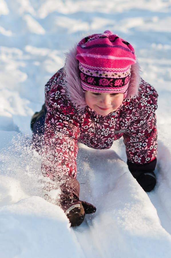 De baby kruipt op sneeuw stock foto's