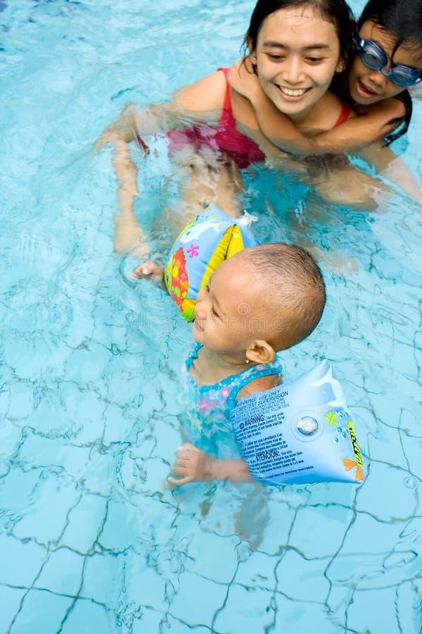 De baby leert om met mamma te zwemmen stock foto's