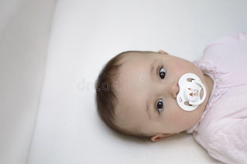 De baby ligt in de voederbak met fopspeen stock afbeeldingen