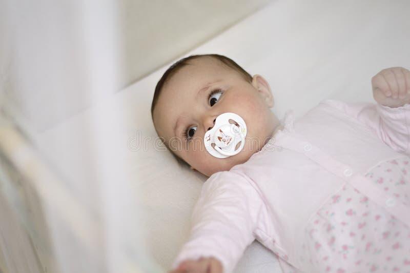 De baby ligt in de voederbak met witte fopspeen stock foto's