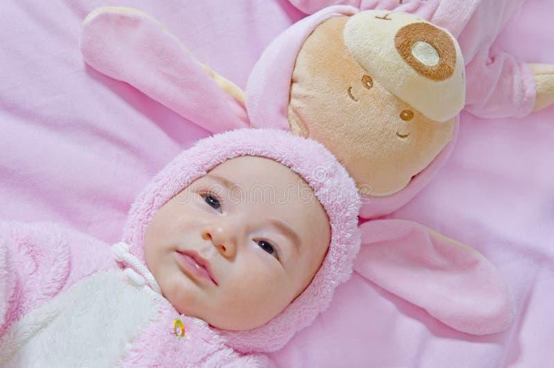 De baby ligt met stuk speelgoed draagt in roze kostuums stock afbeeldingen