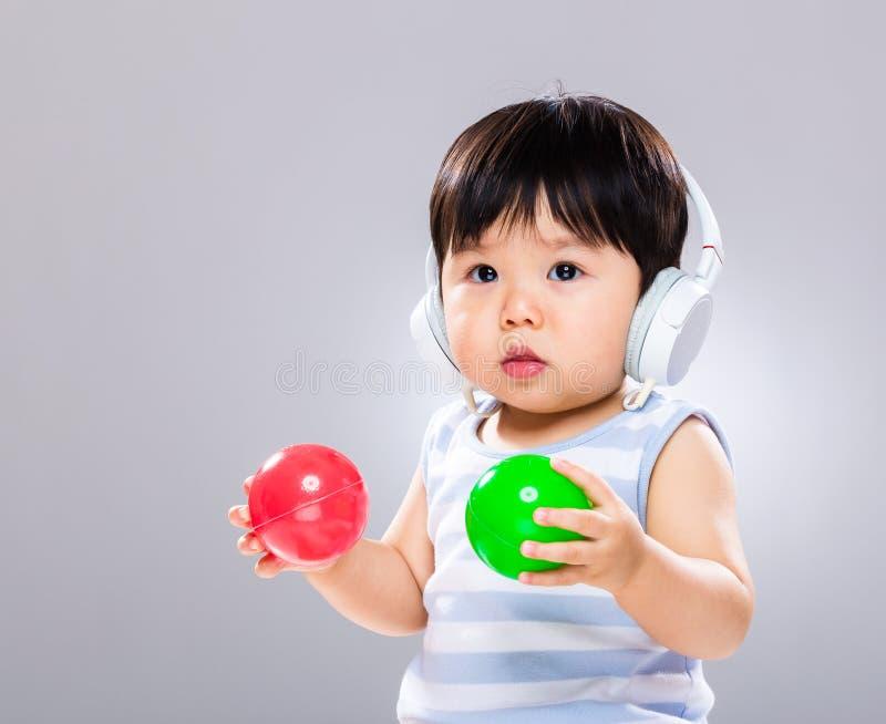 De baby luistert aan muziek en speelt bal royalty-vrije stock fotografie