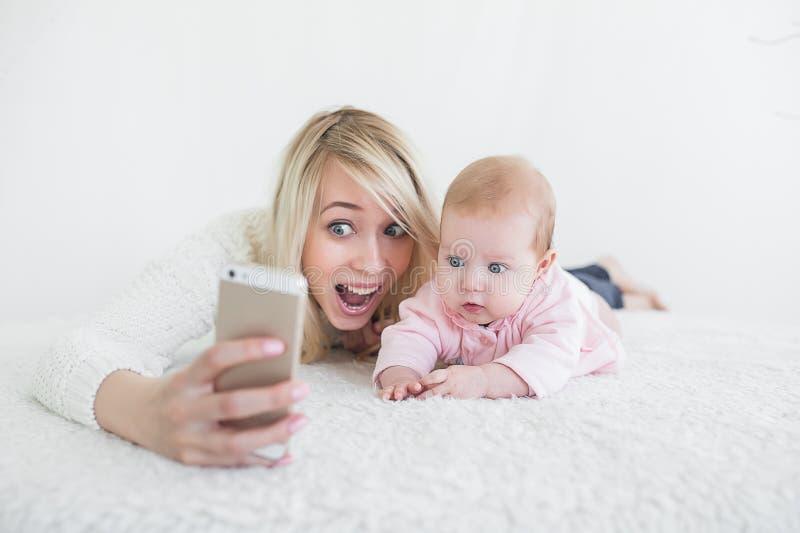 De baby maakt selfie op mobiele telefoon stock afbeeldingen