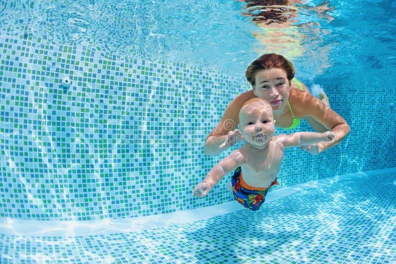 De baby met moeder leert om onderwater in zwembad te zwemmen royalty-vrije stock fotografie