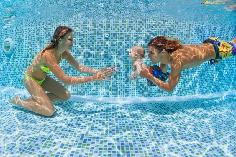 De baby met moeder, vader leert te zwemmen, onderwater duiken royalty-vrije stock foto