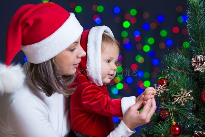 De baby met moeder verfraait Kerstboom op helder royalty-vrije stock fotografie