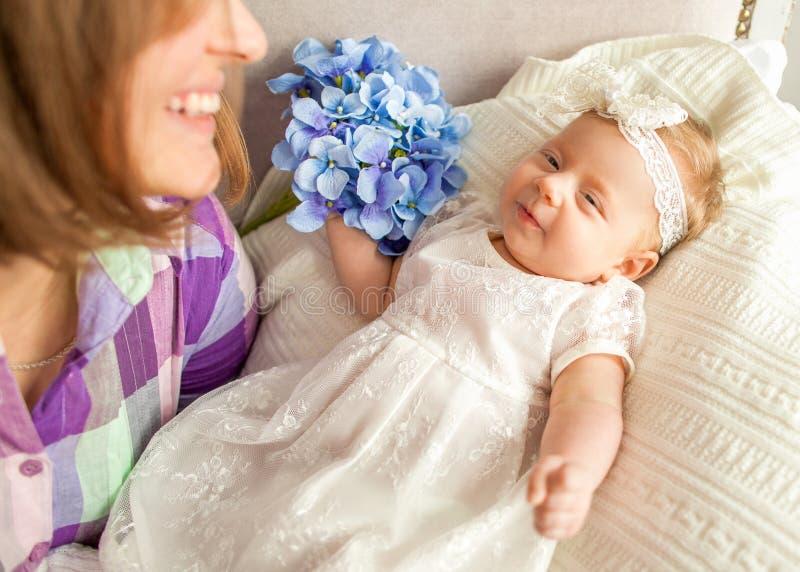 De baby met uw moeders ligt op het bed, moeder` s dag concep royalty-vrije stock afbeelding