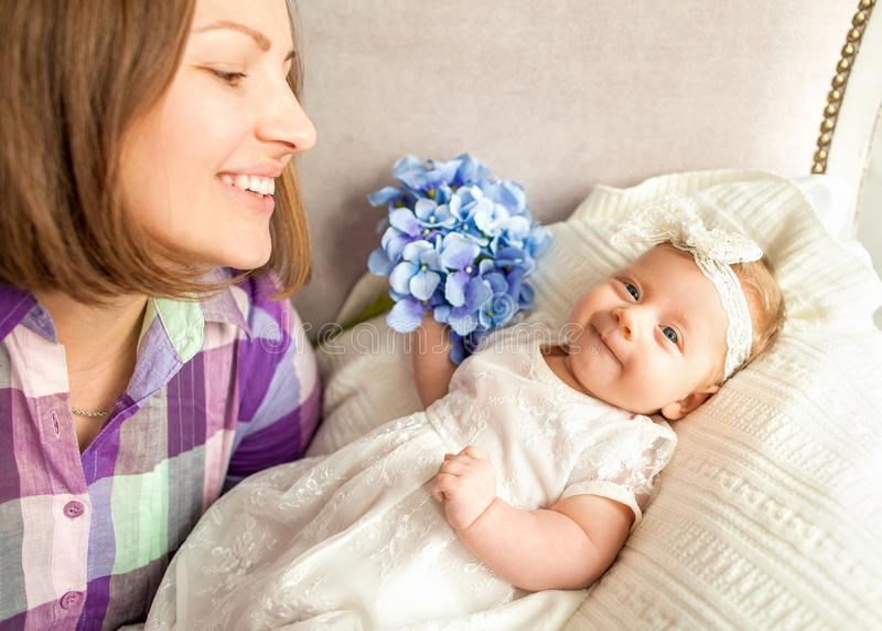 De baby met uw moeders ligt op het bed, moeder` s dag concep stock afbeelding