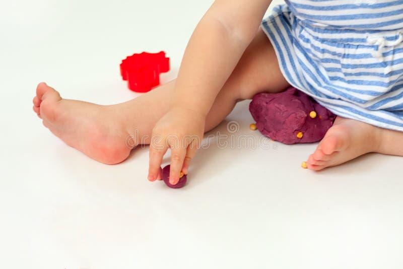 De baby overhandigt vormende plasticine Reeks van plasticine en plastic knipselblok op witte achtergrond stock afbeeldingen