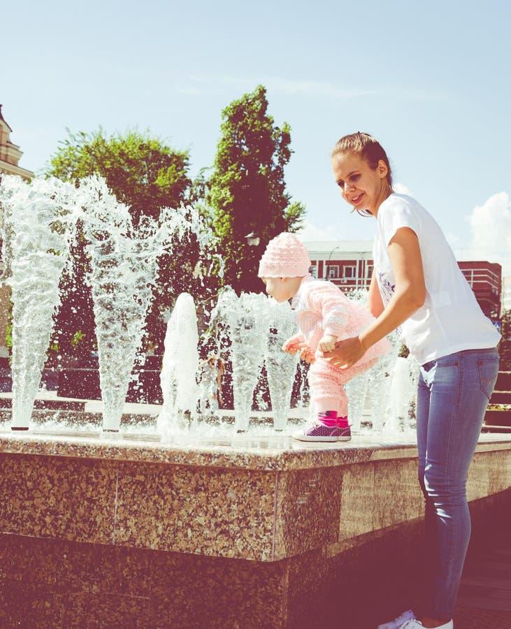 De baby speelt bij de fontein stock foto's