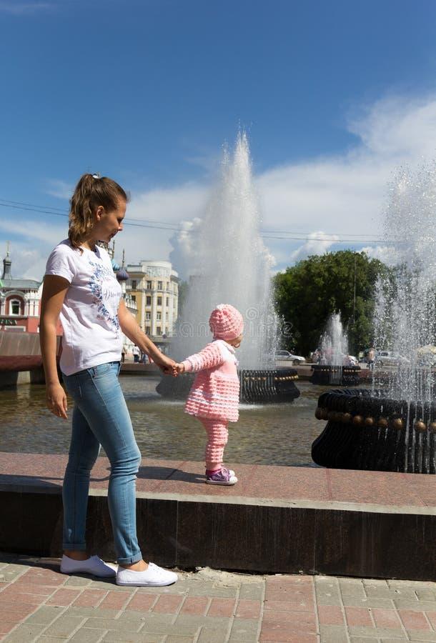 De baby speelt bij de fontein stock foto