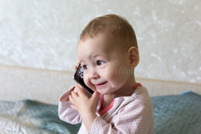 De baby speelt met een smartphone royalty-vrije stock afbeeldingen