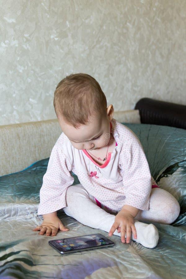 De baby speelt met een smartphone stock foto's