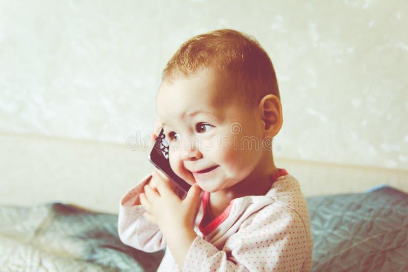 De baby speelt met een smartphone royalty-vrije stock foto