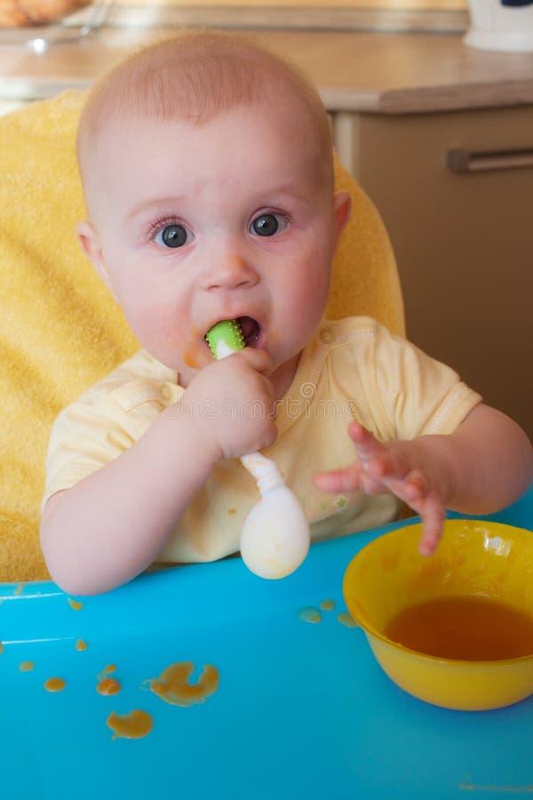 De baby van 7-8 maanden zelf houdt de lepel stock afbeeldingen