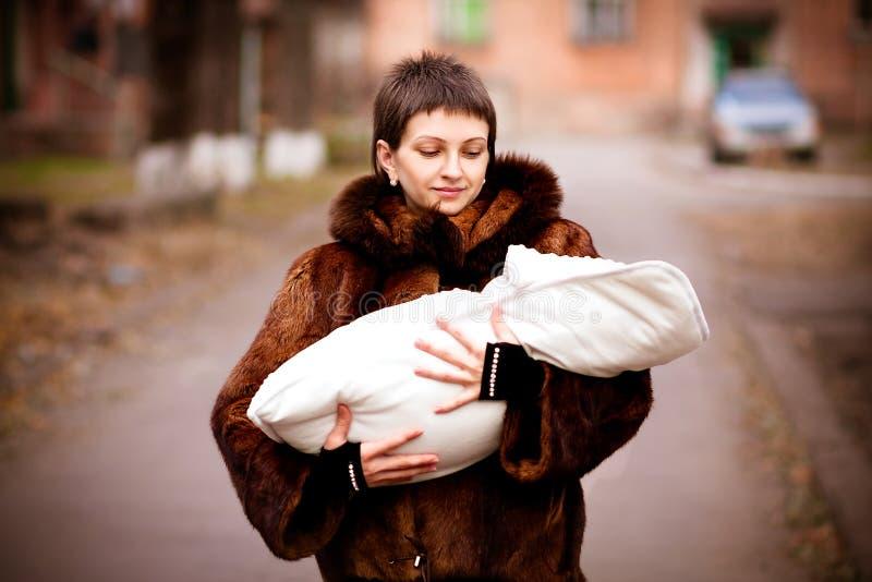 De baby van de moederholding op wapens, in een deken worden verpakt die Zacht nadrukeffect stock fotografie