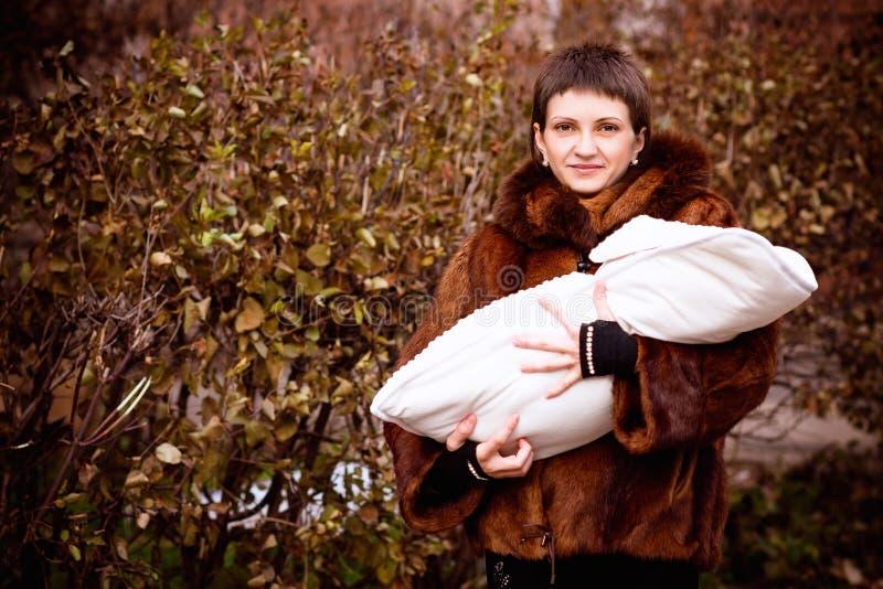 De baby van de moederholding op wapens, in een deken worden verpakt die Zacht nadrukeffect stock foto's