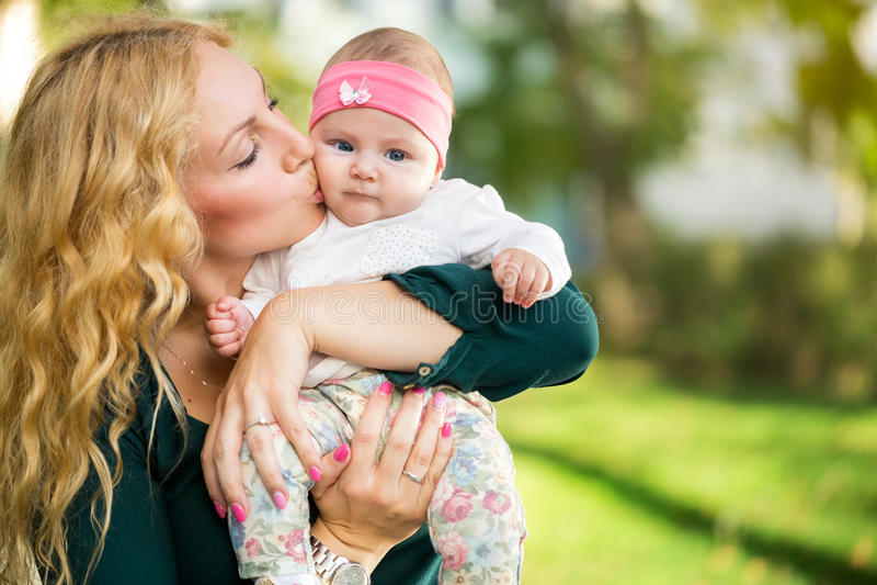 De baby van de moederkus in handen royalty-vrije stock afbeelding