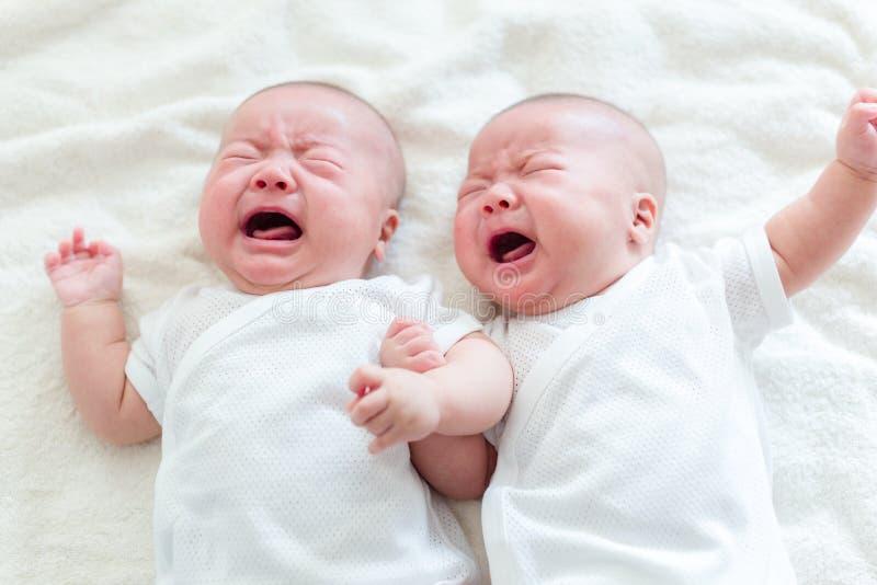 De baby van de tweelingenbroer het schreeuwen stock foto