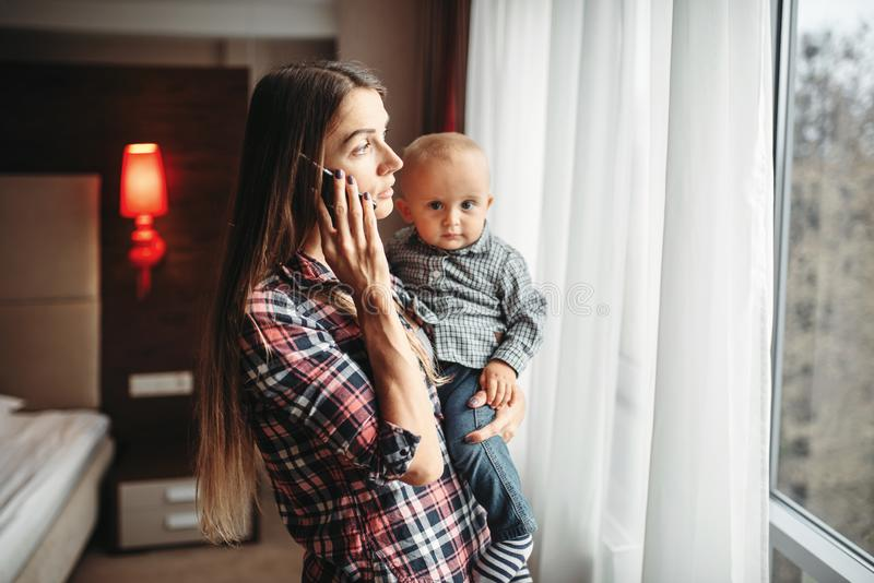 De baby van de moederholding in wapens en het spreken telefonisch royalty-vrije stock foto