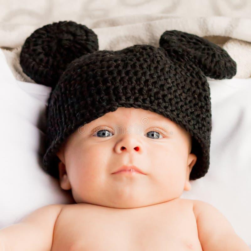 De baby van twee maand met een zwarte wolhoed stock foto