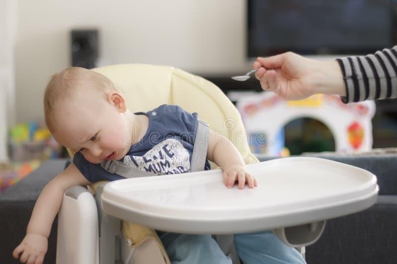 De baby wil niet eten en schreeuwt stock afbeelding