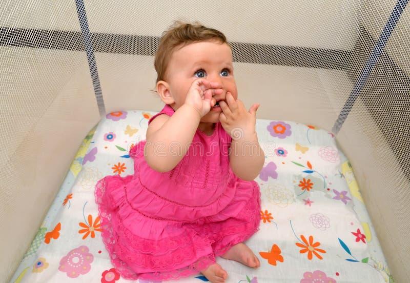 De baby zit in een arena, die duwvingers hebben in een mond royalty-vrije stock afbeelding