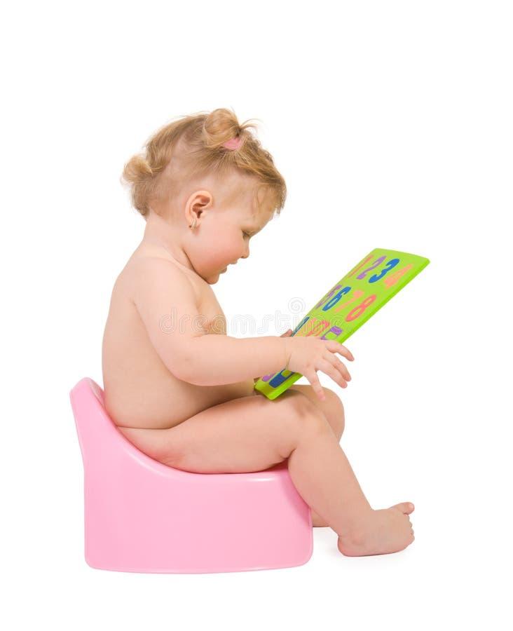 De baby zit op roze onbenullig en kijkt aan cijfersstuk speelgoed