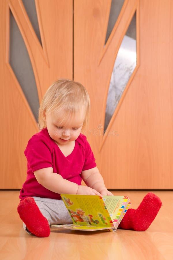 De baby zit op vloer en las babyboek royalty-vrije stock afbeelding