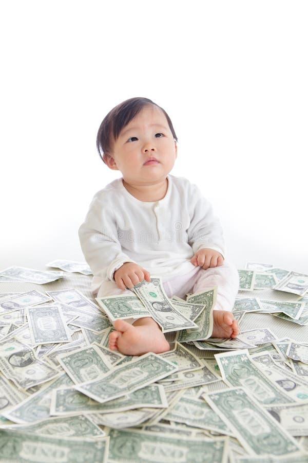 De baby zit op vloer met veel geld stock afbeelding