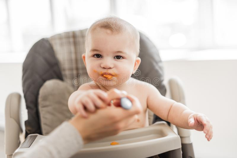 De baby zit op zijn stoel wachtend op diner royalty-vrije stock foto's
