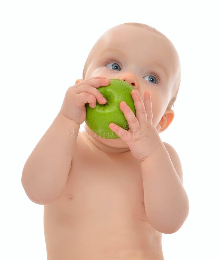 De babyjong geitje die van het zuigelingskind groene appel blauwe ogen eten die t bekijken royalty-vrije stock afbeeldingen