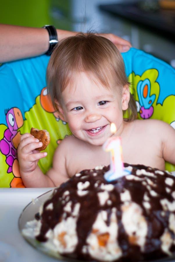 De babyjongen blaast uit kaarsen op een cake royalty-vrije stock fotografie