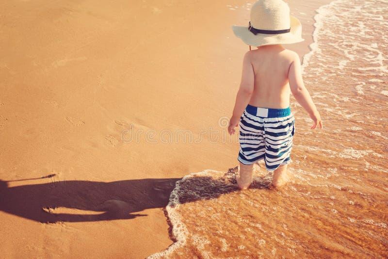 De babyjongen loopt op het strand royalty-vrije stock afbeeldingen