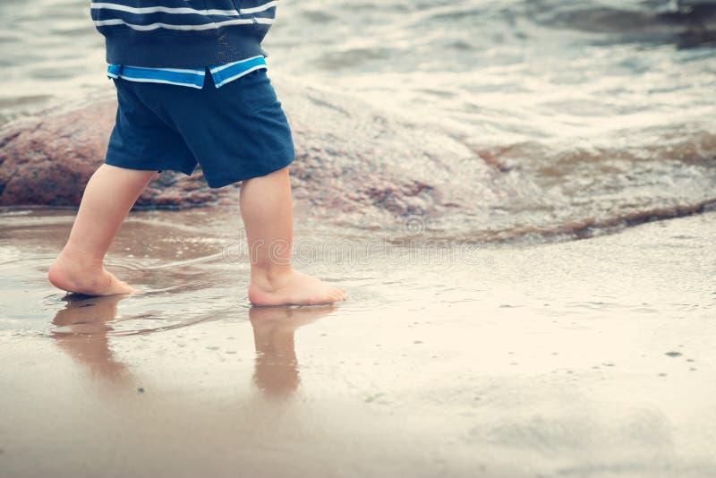 De babyjongen loopt op het strand royalty-vrije stock afbeelding