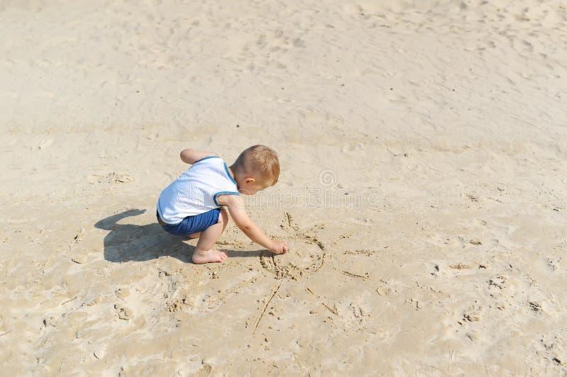 De babyjongen trekt een zon in het zand op het strand stock fotografie