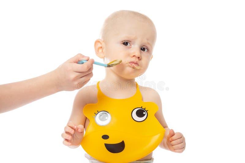 De babyjongen wil fijngestampte havermoutpap geen lepel eten Zuigelingsbaby het stellen in gele slab die op witte achtergrond wor stock afbeelding