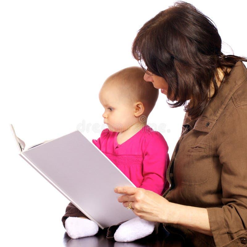 De babymeisje dat van de zuigeling boeken met oma ontdekt stock foto's