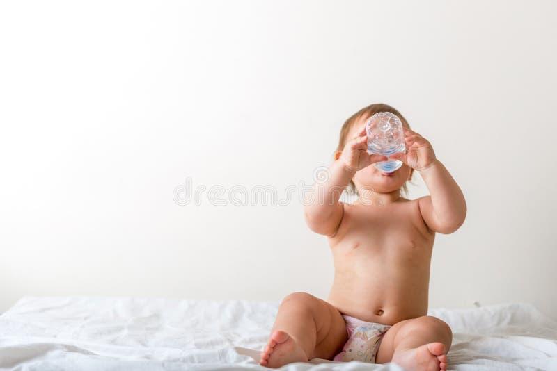 De babypeuter zit op het witte bed, glimlachen en drinkt water van plastic fles De ruimte van het exemplaar stock afbeeldingen