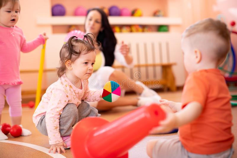 De babys groeperen zich met trainer in gymnastiek royalty-vrije stock foto's