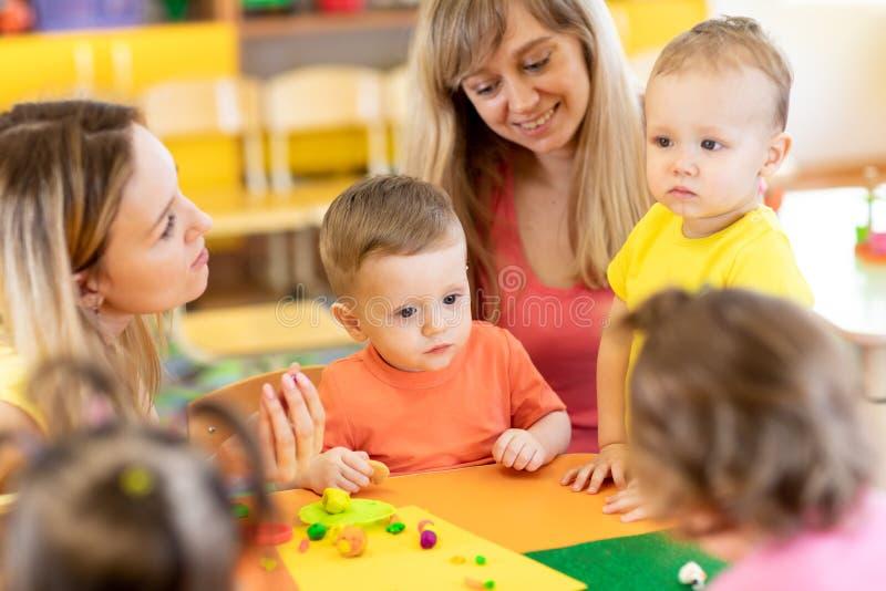 De babys met leraren spelen kleurrijk kleistuk speelgoed in kinderdagverblijf royalty-vrije stock foto
