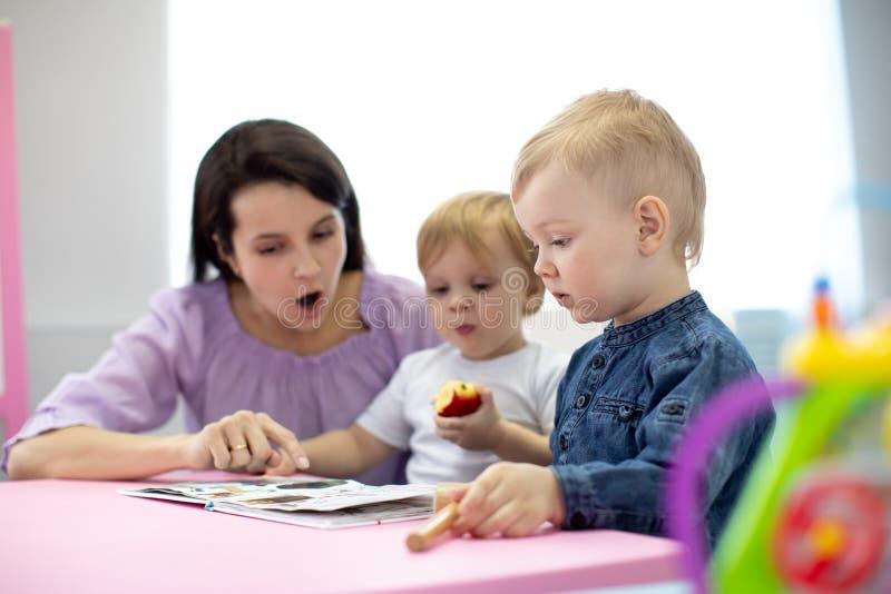 De babysitter leest boek aan jonge geitjes royalty-vrije stock foto