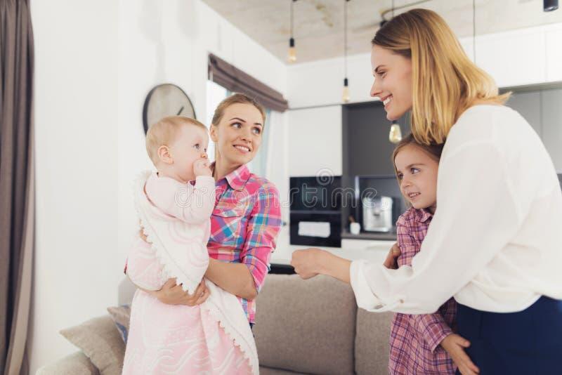 De babysitter ontmoet de moeder van de kinderen, die de baby in haar wapens houden Het oudere meisje koestert Mamma royalty-vrije stock afbeelding