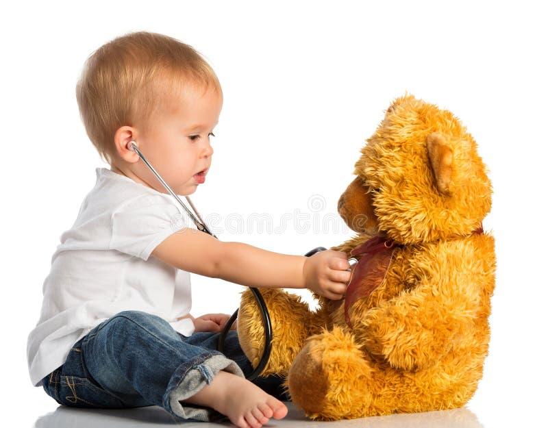 De babyspelen in artsenstuk speelgoed dragen en stethoscoop stock afbeelding