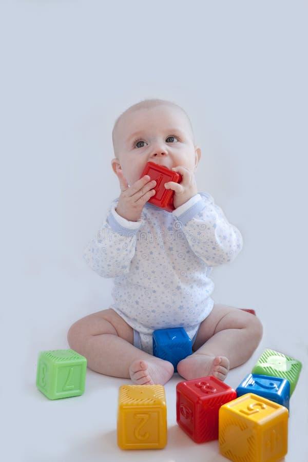 De babyspelen met de multi-coloured kubussen stock afbeelding