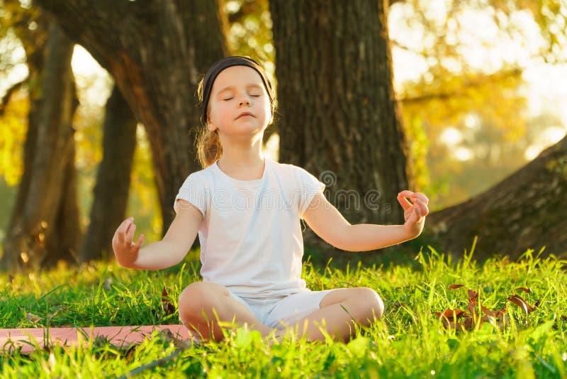 De babyyoga Lotus stelt een kind het praktizeren yoga in openlucht stock afbeelding