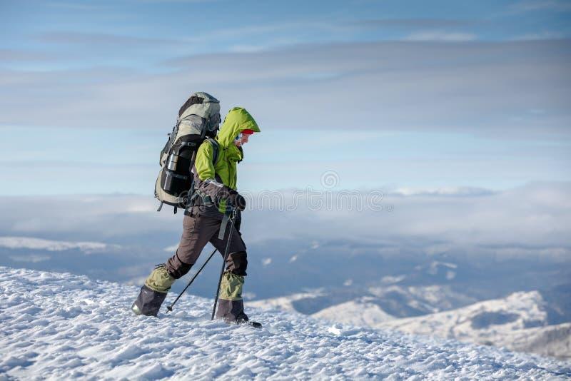 De Backpackervrouw loopt in de winterbergen op zonnige dag stock afbeeldingen